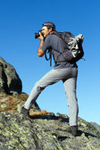 Young tourist taking photos outdoor from the top of the mountain — Stock Photo