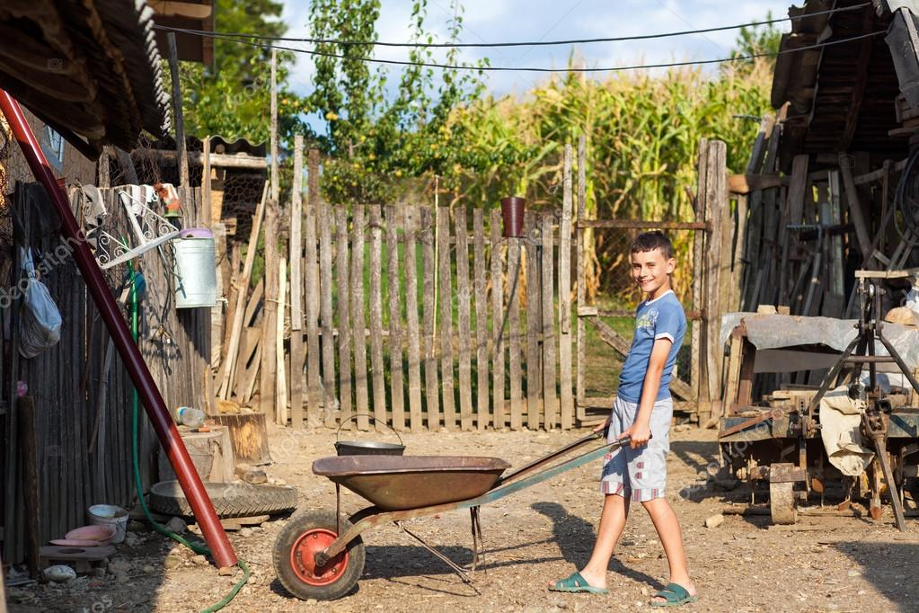 Cute boy pushing a barrow at countryside, doing yard work — Stock Photo #12899674