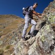 Man hiking on difficult mountain trail - Stockfoto