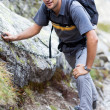 Young man hiking on difficult mountain trail — Stock Photo #12900267