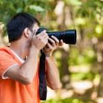 giovane uomo fotografare nel bosco — Foto Stock