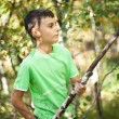 Cute boy playing in the thicket with a stick - Stock Photo