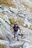 Young man hiking on mountain trail — Stock Photo