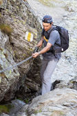 Young man hiking on difficult mountain trail — Stock Photo
