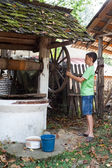 Schoolboy getting water from well — Stockfoto