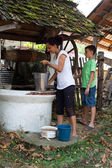 Mother and son getting water from well — Stockfoto