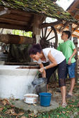 Mother and son getting water from well — Stock Photo