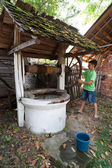 Schoolboy getting water from well — Stock Photo