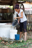 Woman getting water from well — Stockfoto