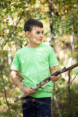 Cute boy playing in the thicket with a stick — Stock Photo