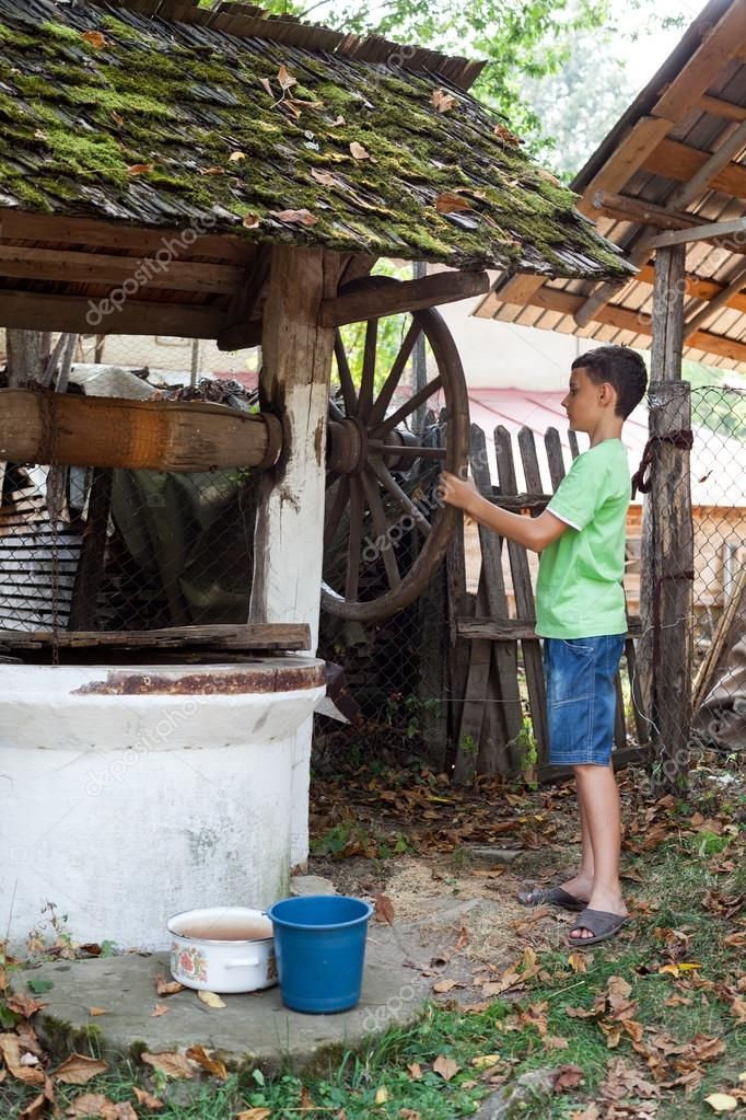 Schoolboy outdoor getting water from a vintage wooden well with pulley  Stock Photo #12900386