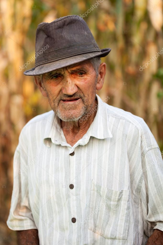 Closeup portrait of a pensive senior man, outside in front of a corn field  Stock Photo #12900572