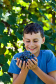Happy schoolboy with hands full of grapes — Stock Photo