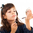 Little girl using lipstick while looking in the mirror — Stock Photo #13757587