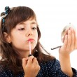 Little girl using lipstick while looking in the mirror — Stock Photo