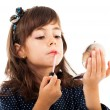 Little girl using lipstick while looking in the mirror — Stock Photo #13757603