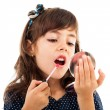 Little girl using lipstick while looking in the mirror — Stock Photo #13757605