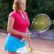 Young woman holding a tennis racket and balls — Stock Photo