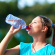 Young sportswoman drinking water from bottle — Stock Photo #13757701