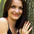 Happy young woman leaning on tree trunk — Stock Photo #13757767
