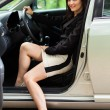 Happy young woman sitting in new car — Stock fotografie #13757815