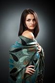 Beautiful young woman with hand on hip wearing shawl — Stock Photo