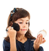 Little girl using face powder while looking in the mirror — Stock Photo