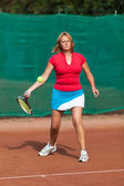 Young woman playing tennis on a dross field — Stock Photo