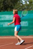 Joven jugando al tenis en un campo de escoria — Foto de Stock