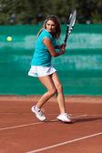 Młoda kobieta, grać w tenisa na polu żużel — Zdjęcie stockowe