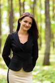 Young businesswoman standing in the woods — Stock Photo