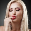 Beautiful blond woman sucking her finger — Stock Photo