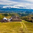 Landscape with a wooden traditional house and mountains in the b — Stock Photo
