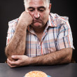 Unhappy man looking at burger — Stock Photo