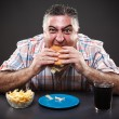 Greedy man eating burger - Stock Photo