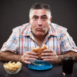 Foto Stock: Greedy man eating burger