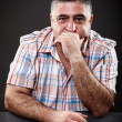 Mature man thinking while sitting at table — Stockfoto