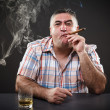 Mature mafia man drinking and smoking while sitting at table - Stock Photo