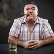 Stock Photo: Mature mafia man drinking and smoking while sitting at table
