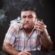 Mature mafia man drinking and smoking while sitting at table — Stock Photo