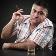 图库照片: Mature mafia man drinking and smoking while sitting at table