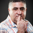 Fat man making silence gesture in studio — Stock Photo