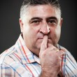Fat man making silence gesture in studio - Stock Photo