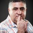 Fat man making silence gesture in studio — Stock Photo