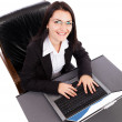 Happy young businesswoman working on laptop while sitting in an — Stock Photo