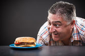 Greedy man looking at burger — Stock Photo