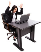 Angry businesswoman sitting at desk while using a laptop — Stock Photo