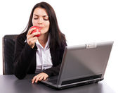 Young businesswoman eating an apple while sitting at office desk — Stock Photo
