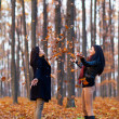 Two young girlfriends playing with dried leaves in the woods — Stockfoto