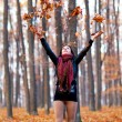 Young woman playing with dried leaves in the woods - Stock Photo